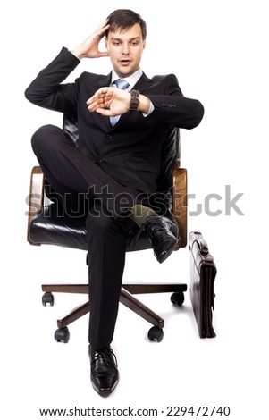 Young businessman checking the time while waiting in the armchair over white background - stock photo