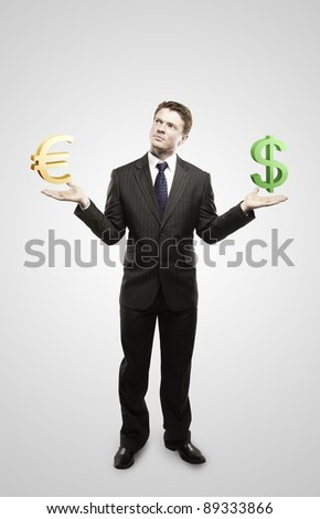 Young  businessman chooses euro or dollar signs.On a gray background - stock photo