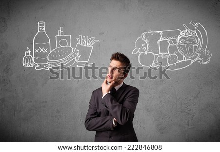 Young businessman choosing between healthy and unhealthy foods - stock photo