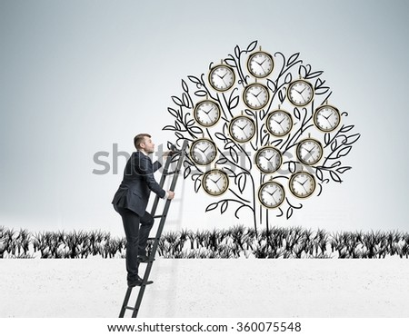 Young businessman climbing a drawn tree with clocks instead of leaves via ladder. Gray background. Concept of timing - stock photo