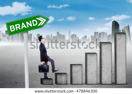 Young businessman climbs staircase while carrying a briefcase with brand text on the signboard