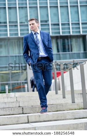 Young businessman coming down stairs with hands in pockets - stock photo
