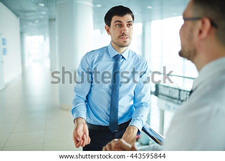 Young businessman communicating with his colleague at office corridor - stock photo