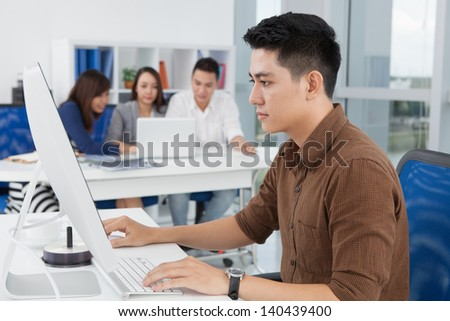 Young businessman concentrated at his network on the foreground - stock photo