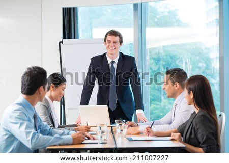 Young businessman conducting meeting with his colleagues
