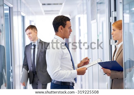 Young businessman consulting his colleague in office - stock photo