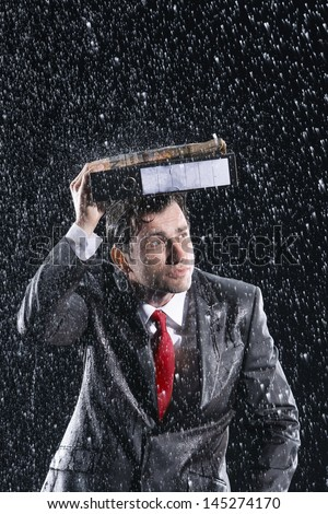 Young businessman covering head with binder in rain - stock photo
