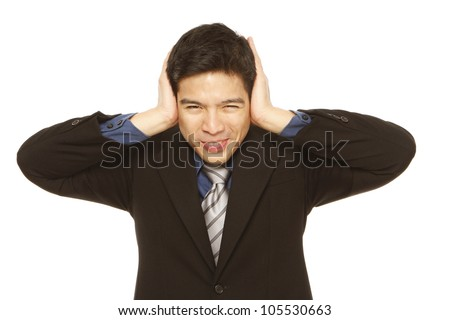 Young businessman covering his ears