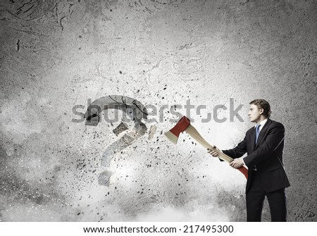 Young businessman crashing question sign with axe - stock photo