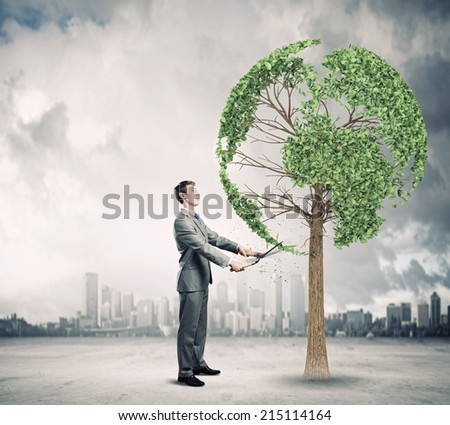 Young businessman cutting tree with scissors in shape of Earth planet - stock photo