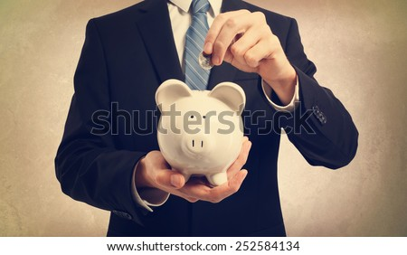 Young businessman depositing money in piggy bank - stock photo