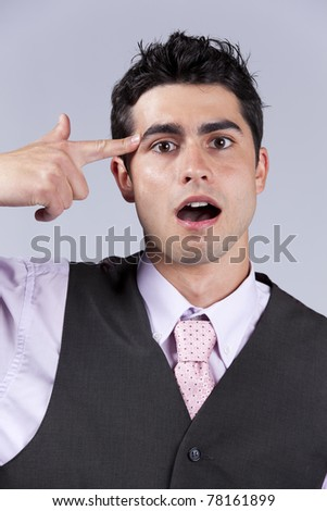 Young businessman despair pointing his finger to his head like shooting a gun - stock photo