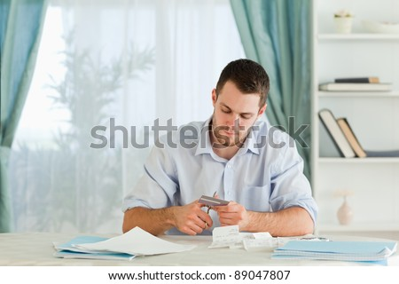 Young businessman destroying his credit card
