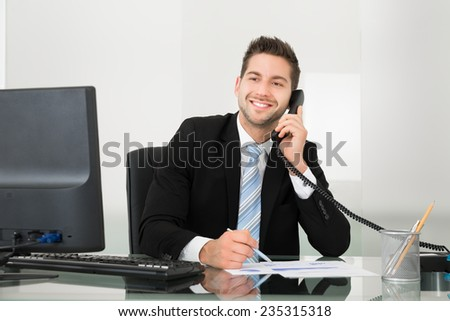 Young businessman discussing over documents on telephone at desk in office - stock photo