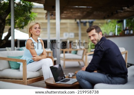 Young businessman discussing plan with female colleague, businesspeople working with laptop sitting in modern place, business meeting of two colleagues outside the office, business and success concept - stock photo