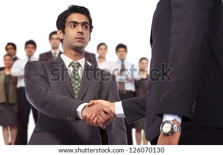 young businessman doing handshake with business people - stock photo