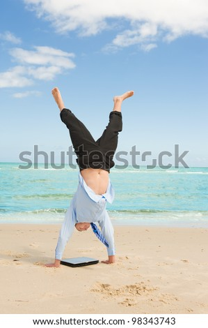young businessman doing handstand on the beach after a big deal