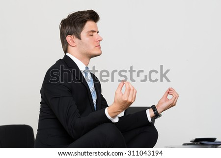 Young Businessman Doing Meditation At Desk In Office