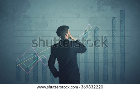 Young businessman drawing chart on wall - stock photo