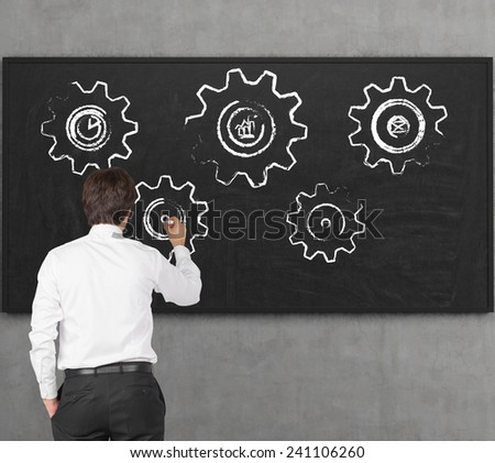 young businessman drawing cog and geers on desk - stock photo