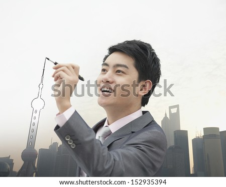 Young Businessman drawing Shanghai skyline - stock photo