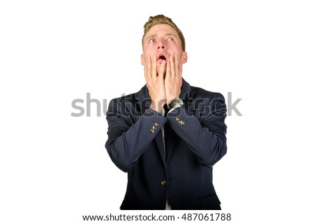 Young businessman dressed in a suit desperate look up isolated on white. Crisis concept.