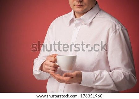 Young businessman drinking a cup of coffee in white shirt over red background
