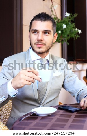 Young businessman drinking a cup of coffee while sitting at a coffee shop terrace table, outdoors and smiling at the camera - stock photo