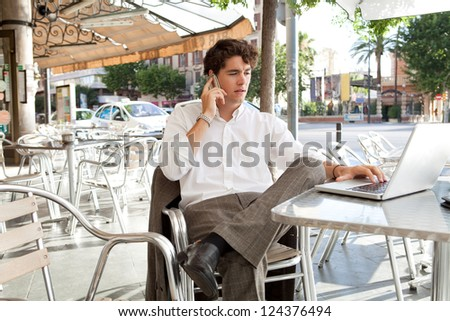 Young businessman drinking a cup of coffee while sitting at a coffee shop terrace table using a laptop computer and making a phone call on his smart phone, outdoors. - stock photo