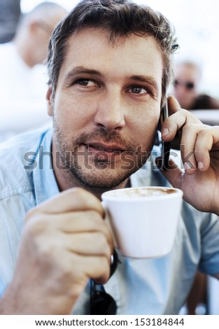 Young businessman drinking coffee and speaking on the phone - stock photo