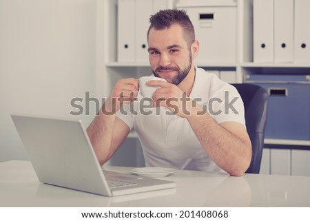 Young businessman drinking coffee in office, toned - stock photo