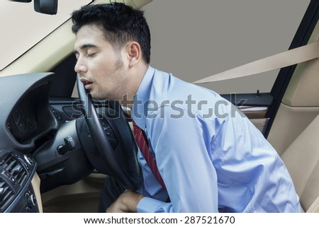 Young businessman driving a car and looks tired, sleeping in the car while wearing the safety belt - stock photo