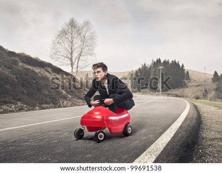 Young businessman driving a toy car on a country road - stock photo