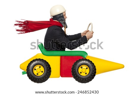 Young businessman driving fast on a toy car - stock photo