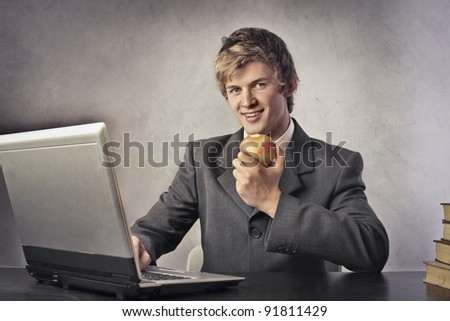 Young businessman eating an apple at office - stock photo