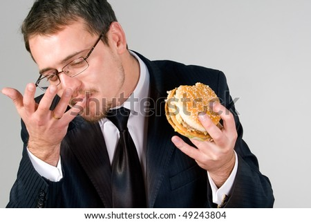 Young  businessman eating hamburger, licking fingers - stock photo