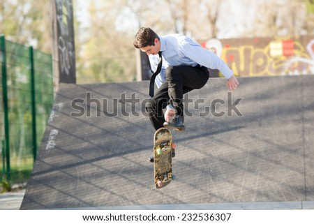 Young businessman, elegantly dressed, photographed at the moment of the jump with the skateboard at the skate park.