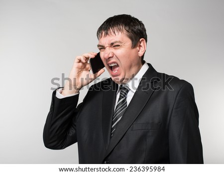 young businessman emotionally speaks on the phone - stock photo