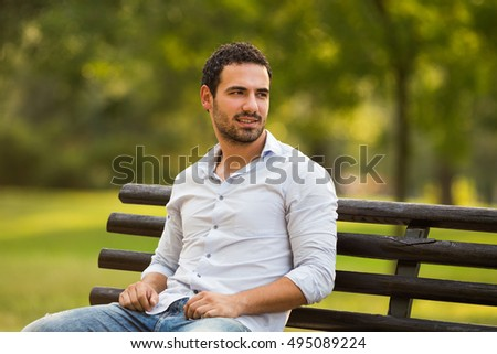 Young businessman enjoys sitting at the park.Young businessman relaxing