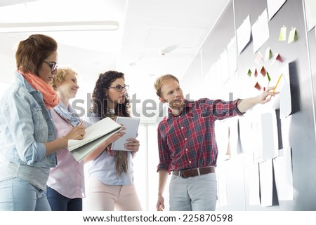 Young businessman explaining document to female colleagues in creative office - stock photo