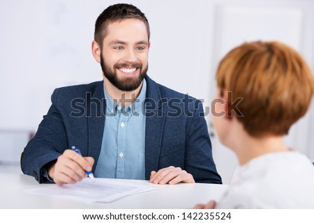 Young businessman explaining documents to female co worker at office desk - stock photo