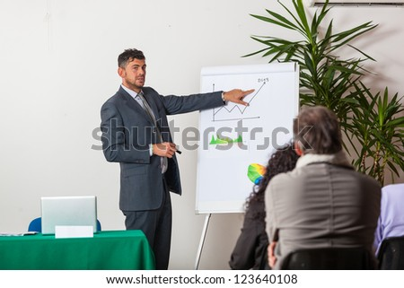 Young Businessman Explaining Plans and Charts - stock photo