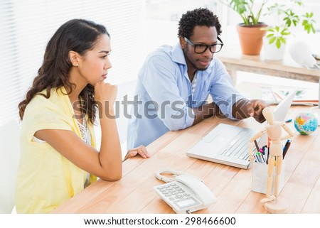 Young businessman explains something to the confused businesswoman in the office - stock photo