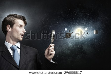 Young businessman exploring planets of sun system