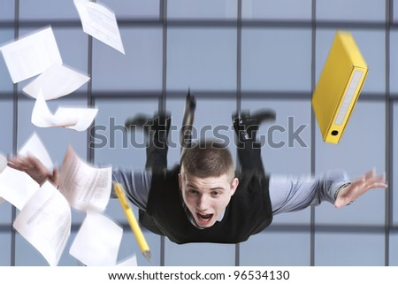 Young businessman falling from the building with his documents - stock photo