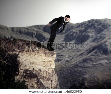 Young businessman falls from the cliff. - stock photo