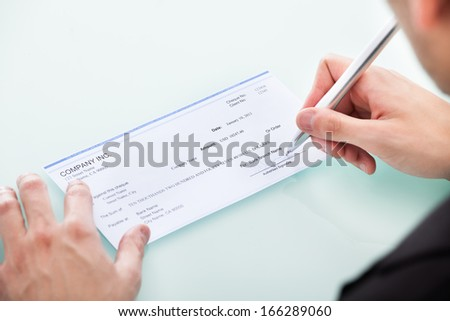 Young Businessman Filling Blank Cheque At Office Desk - stock photo