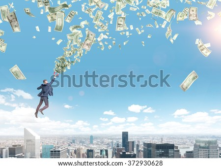young businessman flying over Paris with a magnet in hand that is pulled to money tornado. Paris and blue sky at the background. Concept of strivig for wealth. - stock photo