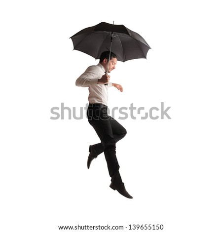 young businessman flying with umbrella - stock photo