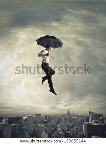 young businessman flying with umbrella over the city - stock photo